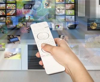 Eine Person steuert mit einer Fernbedienung eine Wand mit digitalen Geräten an.