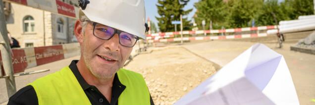 Mitarbeiter liest einen Werkleitungsplan auf der Baustelle