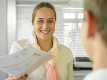 Eine Mitarbeiterin überreicht die neuen Geschäftsbedingungen