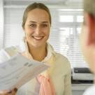 Eine Mitarbeiterin übergibt die neuen AGB